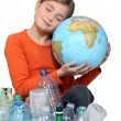 Little girl holding globe and recycling bottles — Stock Photo #16612157