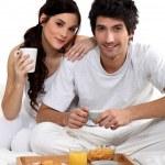 Couple having breakfast in bed — Stock Photo