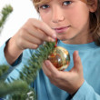 A kid decorating a Christmas tree. — Stock fotografie