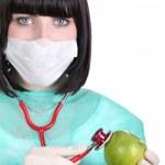 Female doctor holding apple — Stock Photo #16618771