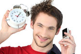 Man holding alarm clock and mobile — Stock Photo