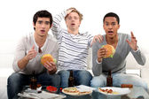 Male trio watching soccer match on TV and eating hamburgers — Stock Photo