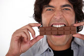 Man playfully eating chocolate — Stock Photo