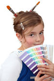 Girl holding a palette of colour samples — Stockfoto