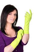 Brunette putting on rubber gloves — Stock Photo