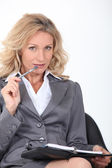 Blond woman chewing pen — Stock Photo