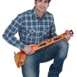 Builder knelt holding spirit level — Stock Photo #16620027