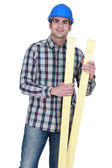 Carpenter holding two planks of wood — Stock Photo