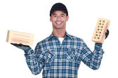 Mason holding a brick in either hand — Stock Photo