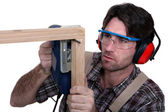 Carpenter sawing into wooden frame — Stock Photo