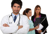Doctor with medical staff in the background — Stock Photo