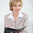 Blond businesswoman sat at desk with diary — Stock Photo