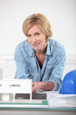 Woman with paper-work and hard hat — Stock Photo