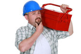 Craftsman holding a tool box and touching his chin — Stockfoto