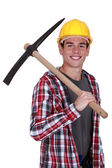 Smiling young man with a pickaxe — Stock Photo