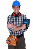 Young tradesman holding a sander — Stock Photo