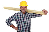 Cheerful carpenter carrying timber — Stock Photo