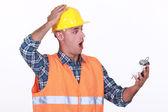 Shocked builder looking at alarm clock — Stock Photo