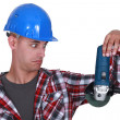 Stock Photo: Uneasy tradesmlooking at angle grinder