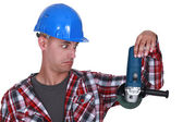 Uneasy tradesman looking at an angle grinder — Stock Photo
