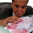 Young businessmwith pile of cash — Stock Photo #16724583