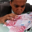 Avid businessman looking at the banknotes on his desk - Photo
