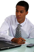 Young Afro-American businessman working at his desk — Stock Photo