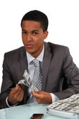 Young businessman counting money — Stock Photo