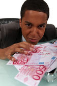 Young businessman with a pile of cash — Stock Photo