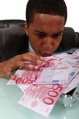 Avid businessman looking at the banknotes on his desk — Stock Photo