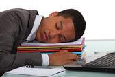 Trabajador durmiendo en una pila de carpetas — Foto de Stock