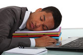 Worker sleeping on a stack of folders — Stock Photo