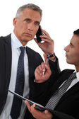Man on the phone and writing assistant — Stock Photo