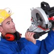 Stock Photo: Construction worker examining his circular saw.