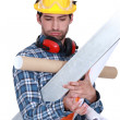 Stock Photo: Construction worker overloaded with tools and building materials