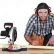 Man with band saw marking wood - Stock Photo