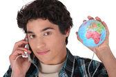 Joven con su teléfono enchufado en el mundo — Foto de Stock