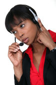 African American woman answering the hotline. — Stock Photo