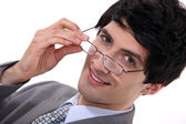 Businessman peering over his glasses — Stockfoto