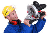 Construction worker examining his circular saw. — Stock Photo