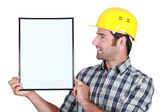 Young helmeted blue collar in profile holding copyspace — Stock Photo