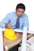 Architect with his fist on a hard hat — Stock Photo