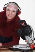 A mature carpenter with a circular saw. — Stock Photo
