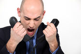 Bald man shouting into two telephones — Stock Photo