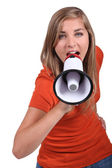Girl shouting into loud speaker — Stock Photo