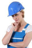 Nadenkend vrouw in overall en een hard hat — Stockfoto