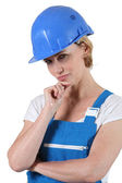 Pensive woman in overalls and a hard hat — Stockfoto
