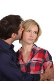 Man whispering in an unhappy woman — Stock Photo