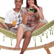 Couple sat on hammock with cocktails - Stockfoto