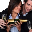 Couple celebrating with a glass of wine - Stock Photo